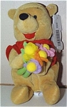The Disney Flower Pooh bear mini-bean bag plush, holds a colorful bouquet of cloth flowers and was intended for Mother's Day when he was produced in about 1997. He is dressed in his red 'Pooh' shirt, and he has a Mousketoys tag from Disneyland. He is approximately 7 to 8 inches tall. Retired bean bag is new, and mint with tag.