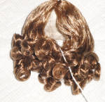 Light Brown (More Medium Brown) Kelly synthetic adjustable replacement wig with mid-length curls and a center part for 3.5 to 5 inch circumference hard plastic and composition doll heads.  This wig can adjust to fit a variety of dolls such as Tiny Betsy McCall, Vogue Ginny and Jill, Madame Alexander Alexander-kins and Cissette, Nancy Ann Storybook Muffie, Ginger, Pam, and many other 7.5 to 10.5 inch dolls.  It is in an attractive style. Manufactured for Dollsparts. The price is only for the wig, and not the doll modeling this style wig in a different color. New, mint-in-package.  Expand listing to view all 3 photographs.