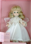 1989 Effanbee 9 inch Li'l Innocents soft vinyl Christina angel doll, has blonde rooted hair styled in a flip, and moving blue eyes. She is wearing a long white lace-trimmed dress with gold trim and white wings. Old stock that is mint-in-the-box, and comes with a plastic stand. Effanbee is not making dolls from this sweet mold at this time.