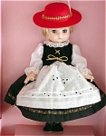 This 1989 Effanbee 9 inch Li'l Innocents Germany vinyl doll has long blonde rooted hair, moving blue eyes, and a sweet, serious face. Her German national costume includes a black dress with colorful braid trim, a white eyelet apron, a long sleeved white blouse with lace trim, a black felt vest with gold ties, a red felt hat with a gold band and white feather, and black shoes.  A plastic stand is included. Effanbee is not currently making dolls from this mold. New, mint-in-the box. Expand listing to view both photographs.