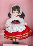 This 1989 Effanbee 9 inch Li'l Innocents soft vinyl doll is dressed in the international costume of Italy, has brunette rooted hair, and moving vinyl brown eyes. Her Italian national costume includes a red skirt with green and yellow braid trim, a white blouse, a white apron, a white scarf, a black velvet belt with red ribbon, and black shoes.  Effanbee is not currently making dolls with this sweet mold. Doll comes with a plastic stand. New and mint-in-the-box.