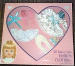 Effanbee 1989 White and Aqua Party Dress Outfit for 9 inch Li'l Innocents dolls includes a white satin dress with lace trim, an aqua collar; sash and hair bows; white shoes with aqua bows; white tights; and a pink plastic doll comb and brush. L'il Innocents outfits will also fit 9 inch Sammie dolls. New, mint-in-the-box old stock.