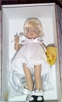 Effanbee vinyl 2003 Purely Patsyette blonde doll, No. PY0301 is from 2003, is a Robert Tonner design.  This 8.5 inch Purely Patsyette doll has short pale blonde rooted hair, painted blue side-glancing eyes, and a sweet wistful face. She comes with a plastic stand and gold heart chain. She is wearing only a white bodysuit, white chemise, and black leatherette-type shoes with socks. Separate outfits are available. The earlier 2003 and 2004 Patsyette dolls, like this one, are about an inch smaller and more slender than the later Patsyette dolls with moving eyes were. Old stock in mint-in-the box condition.