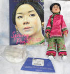 This is a 9 inch vinyl artist doll, Spring Pearl of the of Girls of Many Lands Collection by American Girl, which includes an all original doll, doll stand, and the 214 page paperback book, Spring Pearl: The Last Flower', by Laurence Yep. The doll has tan coloring, brunette hair put up in a bun with a silver leaf hairpin, painted brown eyes, and golden earrings. She is wearing she is wearing an exquisite, one of a kind one aoku or tunic and trousers. The rich pink and green silk is embroidered with camellias, a symbol of spring. Tiny frogs or knots hold the jacket closed. Her feet were not bound as were those of many other 12 year old girls in China in the mid 19th century,and she has green silk slippers with pink floral motifs on platforms. She wears this costume that her mother made before she died as she walked across China to the Sung household as an orphan where she was teased about the size of her feet until they saved the family. The preowned set is missing its display container, but the doll is in near mint condition and the book is near mint except for a crinkle at the bottom of the front cover, and can be easily enjoyed free of the restrictive case. This is one of the most difficult to find of the dolls in this set. Expand listing to view all 8 photographs.