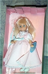 Horsman 1988-89 Melissa Seasons 8 inch Spring doll, is an 8 inch vinyl doll from a mold similar to Sunrise in America, has long blonde rooted hair and moving blue eyes. Her outfit includes a long pink with white dotted swiss dress with matching cloth bonnet with white lace and pastel blue ribbon trim, white shoes, and plastic stand. New, and mint-in-the-box with tag.
