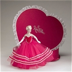 Tonner 2005 Valentine Hearts Hat Box Set Tiny Kitty Collier, No. KT6404, 10 inch fashion doll, has pale blonde hair put up with red flowers, painted blue eyes, and jointed knees. She comes in a red satin covered heart-shaped box edged with white lace. This Kitty is perfect for Valentine's Day. She is wearing a red tulle ball gown trimmed in velvet and white with a heart bodice, long white gloves, red earrings, and heels. Included with her is a box with miniature red long-stemmed roses. Limited edition old stock doll set is new and mint-in-the-box, though outer shipping box may show wear from age. Expand listing to view both catalog photographs and the 3 live photographs.