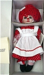 Marie Osmond 1995 12 inch Rosie from 'Twins' series, is an adorable Raggedy Ann-type girl doll with bisque (porcelain) head and hands, while the rest of body is soft fabric. She has bright red curly yarn wig with a large white bow, fixed brown glass-like eyes, eyelashes, a red nose, and red lips. Her Raggedy-style costume includesa red dress with white hearts print, white pinafore with red rickrack trim, white pantaloons with red bows. Her cloth legs are red and white peppermint-type striped like Raggedy Ann's stockings with black feet like Raggedy shoes. This doll has her tag, certificate and a bracelet. Marketed by Knickerbocker. Doll was pre-owned, but this retired doll is in near mint-in-the-box condition. Doll is perfect and the same as new, as is the tag, certificate, and bracelet. Some of the paper inside the box is torn, but everything else is perfect. Expand listing to view both photographs.