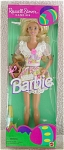 1995 Russell Stover Candies open-mouth smiling blonde 11.5 inch vinyl Barbie fashion doll with blue painted eyes and white pearl-look earrings. She is celebrating Easter wearing a colorful pink, lavender, green, and other pastel colors floral mini-dress with white eyelet ruffle collar with deep pink cloth rose, and straw hat. Barbie is holding a basket. The Easter candy is down in the box. New, mint, and never-removed-from-the-box.