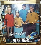 1996 Mattel Star Trek Barbie and Ken Doll Set are boxed as part of the crew of the Enterprise starship in Classic Star Trek. The 11.5 inch Barbie doll has blonde hair and a smiling face. She is wearing a short red dress-style uniform as the female crew members on the classic Star Trek Enterprise wore in the middle to late 1960s television series. The 12 inch Ken has brown molded and sprayed hair. He is dressed in a classic Star Trek Uniform with a gold shirt and dark pants. Both dolls have Star Trek communication badges. The box shows the bridge of Enterprise with Captain Kirk and Commander Spock pictures based on actors who played the parts. Let's hope these newcomers on the bridge don't get killed. Mint, and never removed from the box old stock in like-new condition. Box may show minor wear.