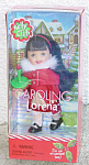 Mattel 2001 Kelly Club Caroling Lorena doll ornament, is listed as used, but looks new, as never removed from box, box has minor denting. This 4.5 inch friend of of Kelly has black hair with bangs and a red hairband, grayish painted eyes, and an open mouth. She is wearing a red coat with white imitation fur collar slit in front to reveal a golden  dress with red velvet and white lace edging, sheer white hose, and black shoes. She is carrying a green candle. A decorated neighborhood is in the background. The box has a Christmas tree background.  She is preowned, but unused and still looks new.