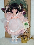 Chris Miller designed Tanzherine for Pittsburgh Originals around 1995. This vinyl doll is a 14 inch, flower fairy, has a sweet serious face (the same as a favorite Robin Woods sculpt), a brunette wig with lavender and white floral hair wreath, and painted green eyes. Her costume includes a peach dress with a white over skirt, lavender and green leaf wings, white slippers with peach rosebud, and she is holding a metal water can. Limited edition of 1000. Mint-in-the-box old stock with certificate, tag, and an adjustable coated metal stand. Expand listing to view all 4 photographs and the catalog picture.