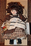 Pittsburgh Originals by Chris Miller 8 soft vinyl Jo doll from the 'Little Women' book by Louisa May from approximately 1996, with an impish face, brunette curls, and green painted eyes. Her outfit includes a brown checked dress with a tan, green, and red plaid underskirt, lacy cream apron with black trim, and she is carrying an apple. An adjustable metal stand is included. New, mint-in-the-box old stock.