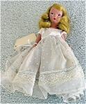 Late 1940s-early 1950s 5.5 inch Nancy Ann Storybook doll with hard plastic slender body etched with 'Storybook Dolls USA', and moving arms, legs, and head. This transitional doll's arms appear to be bisque. She is from the late 1940s or early 1950s. She has painted blue eyes with black pupils and painted lashes. Her blonde mohair wig is in excellent condition and has a side part. Her original 'Starlight, Starbright' outfit includes a long white dress with silver dots print and silver piping trim, white satin underskirt and plain white pantaloons. The pantaloons are closed with a pin while the skirt snaps on. She does not have a head dress or ribbon. This doll is in excellent condition except for her missing hair decorations.