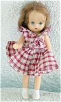 1950s 5.5 inch Nancy Ann Storybook all hard plastic little girl doll with moving head, arms, legs, moving blue eyes, a good auburn wig with center part, and white painted-on boot-type shoes. She is wearing a red and white checked pinafore-style dress that closes in the back with a pin and short white panties. We do not know if this is original or the efforts of an outstanding seamstress, as there is no slip attached. Very good condition.