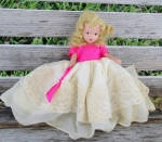 6.5 inch Nancy Ann Storybook all bisque, vintage doll with frozen legs, moving arms, and a movable socket head from the early 1940s, has blurred marking on back of body, an excellent blonde mohair wig, blue painted with black center eyes, and painted-on black shoes. She is likely to be from the Doll of the Month Series. Her outfit includes her original long, full dress with an attached cotton slip, off-white lace-trimmed skirt, and bright pink bodice and ribbon on the skirt.  Doll has her original pantaloons, and dress is closed with pin. This one does not have a hat or hair ribbon, so the hair decoration is probably missing. This beautiful doll is in excellent condition. Expand listing to view both photographs.