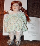 1996 Valerie by Vivian Ohms is a German artist doll that was marketed by European Artist Dolls, and she is 13 inches tall. This artist doll has a bisque head, bisque hands, and bisque legs; a stuffed body, a wig that is light reddish brown styled in braids; stationery green glass eyes, and a sweet facial expression. She is wearing a long sleeved green and white striped with pink and yellow floral print dress, and black patent shoes. Limited to 250 dolls, new, and mint-in-the-box. Expand listing to view both photographs.