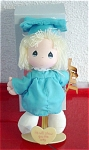 Applause Precious Moments 1989 all cloth 7 inch Graduation doll, Susie, includes a plastic stand that says: 'May Heaven Bless Your Climb to Success.'  She has blonde yarn hair, painted blue teardrop eyes, and a smiling face. She is wearing a blue graduation cap and gown and holding a ladder.
