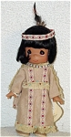 Precious Moments Company 9 inch vinyl Children of the World doll, Morning Glory, from 1995 is a tan-skinned American Indian (Native American), has short rooted black hair, painted dark teardrop-shaped eyes, and a smiling face. She is wearing a leather dress with blue and red braid fringe, beads, and a headband with feather. Retired doll is in new and mint condition.