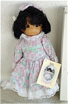 Precious Moments Company 16 inch vinyl and cloth Bethany doll has tan coloring, rooted black hair styled in curly double ponytails with white flowers, a smiling face, and painted dark teardrop-shaped eyes. She could be an African-American or Hispanic girl. She is wearing a long pink and green print Victorian-style dress with white lace trim, a large matching print hair bow, and white shoes with pink pearl button. Introduced in 1991 and retired in 1995. New and mint, with a Precious Moments gift box. Expand listing to view both photographs.