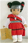 Precious Moments Vinyl and Cloth Native American 12 inch Hopi Girl doll, No. 1483, 1994-1996, is named Yamka which means 'Flower Budding.'  She has tan skin, black double ponytails, dark teardrop-shaped eyes, and a smiling face. This American Indian, or Native American, girl doll's costume incudes a red dress with blue and tan braid waist band over a white blouse, turquoise earrings, beads, bracelet, and white boots. This doll is part of a limited edition of 7,500. This retired doll is mint with her tag old stock.