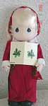 Precious Moments Company 9 inch all vinyl Christmas Caroling Doll issued in 1996, No. 1552 Regina, who has blonde hair, painted blue teardrop-shaped eyes, and a singing mouth. Her Christmas holiday costume consists of a colorful long red dress with a white lace collar, holly print sash, and headband. New, mint condition, with tag, and music.