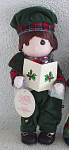 Precious Moments Company 9 inch all vinyl Christmas Caroling Boy Doll issued in 1996, No. 1553 Ian, who has brown hair, painted brown teardrop-shaped eyes, and a singing mouth. His cheerful Christmas holiday costume consists of green corduroy overalls, a red and green plaid shirt, and matching tam. New, mint condition, with tag, and music.
