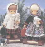 1997 Precious Moments Company set includes 12 inch Gertrude and Natasha wood and fabric two-girl dolls set with wood head with wigs, wood hands, stuffed bodies and legs. These dolls have high quality craftsmanship, and they were limited to 1,000 each, have matching numbers, come with stands, certificates, bags, and miniature teddy bears. Gertrude has a dark blonde wig with a back braid, and blue painted teardrop-shaped eyes. She is wearing a red and green plaid dress, white knit sweater, white scarf, and brown imitation leather shoes. Natasha has a long pale blonde straight wig, and blue teardrop-shaped eyes. Her outfit includes a white eyelet underskirt; a blue, green, and dusty pink floral print overskirt and scarf; a dark green velvet jacket over a white blouse with burgundy trim; burgundy stockings; and black imitation leather shoes. These immigrant girl dolls are musical and play 'God Bless America'. They represent immigrant girls coming to the United States. New, mint-in-their boxes with certificates.