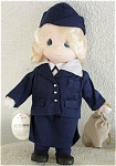 Precious Moments Company cloth and vinyl 12 inch Air Force Girl doll, has pale blonde rooted hair, painted blue teardrop-shaped eyes, and a smiling face. She is dressed in her United States Air Force Uniform including a dark blue skirt, dark blue jacket, dark blue hat, and white blouse. She is carrying her duffel bag. She was first produced in 1997, and retired in 2001. This doll is in new and mint condition.