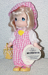 Precious Moments Co. 1998 all vinyl 7 inch Picnic Picnic Rhea, No. 1617, has rooted hair styled in pale blonde curls, painted teardrop shaped blue eyes, and a smiling face. She is dressed in a pink and white checked long pants romper with yellow heart and white puffed sleeves, a matching pink and white checked hat, and yellow shoes with pink bows; and she is carrying a yellow basket. New and mint condition. Expand listing to view both photographs.