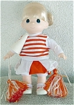 Precious Moments Company 12 inch vinyl and cloth cheerleader doll in orange and white issued in 1998 has a blonde rooted hair styled in a ponytail, painted blue teardrop-shaped eyes, and a smiling face. She is wearing an orange and white skirt over white shorts, an orange and white striped vest over a white shirt, white socks and white with orange sneakers. She is holding orange and white streamers and a white megaphone with orange letters that say 'PM'. Retired doll is new and mint.