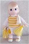Precious Moments Company 12 inch vinyl and cloth cheerleader in yellow and white doll issued in 1998. She has a blonde rooted hair styled in a ponytail, painted blue teardrop-shaped eyes, and a smiling face. She is wearing a yellow and white skirt over white shorts, a yellow and white striped vest over a white shirt, white socks and white with yellow sneakers. She is holding yellow and white streamers and a white megaphone with yellow letters that say 'PM'. Retired doll is new and mint.