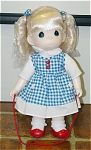 Precious Moments Company vinyl and cloth 12 inch Blonde Cindy doll with Red Jump Rope, 2nd Edition, No. 1450, issued 1998.  This doll has pale blonde rooted hair styled in double bobbed curl ponytails, painted blue tear-drop shaped eyes, and smiling face. She is dressed in a blue and white checked jumper with red heart buttons, pockets with white flower appliques, white blouse, red shoes, white socks, hair ribbons match jumper. Discontinued doll is mint and new. Expand listing to view both the photograph and the catalog picture.
