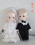 Precious Moments Company 1997-1998 7 inch vinyl Blonde Bride Doll and Groom dolls. Both dolls have painted teardrop-shaped eyes and smiling faces. The bride's hair is put up under a lacy white wedding veil with curls on the side and bangs, and she has blue eyes. Her wedding ensemble also includes a white lace and satin-like wedding dress, and she is holding a pink and white bouquet flowers. The little blonde groom doll has straight hair with bangs, and brown eyes. He is wearing a black tuxedo, white shirt, and a black bow tie. Price is for a set of both dolls. New, mint condition. Expand listing to view both photographs.