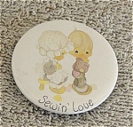 Precious Moments Company Sewin' Love Round Metal Refrigerator Magnet, from the late 1990s. This magnet's artwork depicts a Precious Moments girl sewing a patch of the seat of a boy's pants. If wanted ordering only 1-4 magnets, inquire about lower insured First Class Mail shipping in comments section of the order form. New, mint.