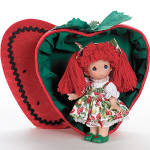 Precious Moments Co. You're a Berry Good Friend, doll set from 2007, No. 2133 is an adorable all vinyl 7 inch Precious Moments doll has red yarn hair in double ponytails with strawberry print hair bows, blue painted teardrop-shaped eyes, and a smiling face. She is dressed in a red and green strawberry print jumper over a white blouse, white pantaloons with red ribbons and green slippers with a strawberry print. She is boxed in a strawberry red with black strawberry speck and rick-rack velveteen heart-shaped box with a green leaf and stem top. This is perfect as a gift for Valentine's Day or a gift of friendship. New and mint.