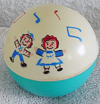 1974 The Bobbs-Merrill Co. Musical Raggedy Ann and Andy Crawl Ball for a baby or a Raggedy collector. This hard plastic ball makes a pleasant musical bell-like ringing sound as it rolls. Its circumference is approximately 12.5 inches. The bottom portion of the ball is teal blue, and the off-white top half has drawings of Raggedy Ann, Raggedy Andy, and musical notes. This ball is displays well Raggedy Ann and Andy dolls or with larger toddler and baby dolls. This ball is in used, but excellent condition, and came from a serious adult collector.