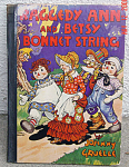 Click here to enlarge image and see more about item RAG0026A: Raggedy Ann and Betsy Bonnet String Hard Cover Book