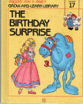 This listing is for the hard cover book, The Birthday Surprise, Volume 17 in Raggedy Ann and Andy's Grow-and-Learn Library. It contains 44 pages with large print and color illustrations on each page. This was copyrighted by Macmillan, Inc. in 1988, and published by Lynx Books. The characters and drawings are based on the creations of Johnny Gruelle.  The book is preowned and gently used. The cover is intact with only faint marks. The pages of the book are intact and mostly in excellent condition, though one of them has faint pencil scribbling across the picture, though it does not prevent reading the page or a good view of picture. The book is meant for a young child to read, though it is also good to read to a child. In this book the dolls plan a birthday surprise for the Camel with Wrinkled Knees when he is at the park. Babbette almost forgets about the flowers for the Camel's party and surprise when she spots a butterfly. She is counted on, and the book teaches about being dependable. When the people are away the dolls, stuffed animals, and young animals come to life and talk and interact with one another in drawings like classical ones. Its ISBN 10 number is 1558021175.