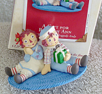 Hallmark Keepsake 2003 A Gift for Raggedy Ann ornament depicts Raggedy Andy holding a gift and sitting against Raggedy Ann on a blue carpet. According to Johnny Gruelle's books the dolls come to life when the people are asleep or out of the house. After Marcella and her family are asleep, Raggedy Andy can wrap a gift for his sister, the loving Raggedy Ann rag doll. This ornament is 2 by 3 inches in size, and it clips on the tree, on a cloth, or other suitable means of display. Mint with box. Expand listing to view both photographs.