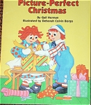 Paperback children's book 'Raggedy Ann's Picture-Perfect Christmas', by Gail Herman and Illustrated by Deborah Colvin Borgo, Random House, Macmillan, Inc., Happy House, from 1988. It has 24 pages and has many color illustrations. According to the story, it is Christmas Eve and Raggedy Ann and the other dolls did not have a gift for Marcella, and they wanted very much to find or make a gift for her. Making a gift was a tremendous challenge for dolls and toys that only came to life when the people were absent or asleep. Nothing seemed quite right until a Santa doll helped them. This book is based on the doll and toy characters created by Johnny Gruelle. Pre-owned book is in excellent condition, and has intact cover and all pages. The ISBN nos. ISBN-10: 039489569X and ISBN-13: 9780394895697.