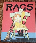 Paperback book, Rags, is a reproduction of antique book by Gallery Graphics, Inc., No. 1303-0002, published in 1995, has 12 pages with color illustrations and a story of a girl rag doll much like Raggedy Ann. This charming children's book is told from the Rag Doll character's point of view her joys and trial. It is illustrated by Fern Bisel Peate. There are no references to an ISBN number for this version of this book anywhere on it or in online references to it. This book was pre-owned by serious Raggedy collector, and is in excellent condition with all pages and intact cover.