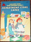 Paperback book, 'Raggedy Ann and Raggedy Andy's Department Store Caper', by Gail George, has Color Illustrations by Deborah Borgo, was published in 1988 by Random House Books for Young Readers, of MacMillan Company, and it has 32 pages. This book tells a story in which Raggedy Ann and Raggedy Andy hid in Marcella's cousin Sally's knitting bag so they could visit the department store. The Raggedy dolls saw many exciting sights at the department store and met new doll friends and toys there. The ISBN Numbers are ISBN-10: 0394894340 and ISBN-13:348. The book has wonderful color illustrations, and it is in excellent condition.