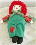 Snowden Christmas holiday 15 inch all-cloth Raggedy Andy doll has a torn tag, but the doll is in clean, crisp, mint condition. He has bright red yarn hair, and he is wearing a green and white sailor hat with embroidered red 'Raggedy Andy', green overalls with red and green patch, red and green patchwork shirt, and green bow, and black sewn-on shoes. His overalls are sewn on his body. He was marketed by Dayton Hudson Corporation as part of Snowden collection. This is a great Christmas version of Raggedy Andy. This Raggedy Andy was pre-owned by serious Raggedy collector; doll is in clean, crisp, excellent condition, but has been on display in a locked glass shop case.