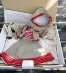 Wee Willie Winkie Brown Traveling Suit costume for Danbury Mint 15 inch vinyl dress-up Shirley Temple dolls, contains a sleeveless brown A-line dress with a red and white striped bodice and red piping trimmed hemline; a brown jacket with red piping and gold buttons trim; a brown beret-style cloth hat with red ribbon, red piping, and a gold button trim; light beige tights; vanilla and black boots with gold buttons; a stand, certificate. This well-made doll outfit was inspired by the costume Shirley wore in this movie in 1937, and is in mint condition in original box, copyrighted in 1996 by 20th Century Fox Corp., and approved by Shirley Temple Black. Wee Willie Winkie when she played Darryl E. Zanuck's adaptation of Rudyard Kipling's tale of British military life in colonial India when she played Priscilla William, was one of Shirley's personal favorites. Outfit has excellent quality. The dresses, hats, shoes, blouses, jackets, and socks fit the Ideal 1972-73 16 inch Shirley Temple dolls, but the pants in this in this series are too snug on them. There are many other outfits in this collection. This is one of the later outfits. Pre-owned by private collector but outfit appears to be unused and in crisp, new mint condition. Box shows wear with torn bottom left corner and spot where price tag was on front. Expand listing to view all 3 photographs.
