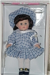 1999 Vogue Century Collection Miss 1910s, hard vinyl 8 inch Ginny doll has brunette hair and moving blue eyes. She is wearing a blue and white plaid drop-waist dress with sailor-type collar, matching cloth hat with wide brim; black leatherette center-snap shoes. A plastic stand that says 'Ginny' and a doll-sized comb and brush are included. Retired doll is new and mint-in-the-box, though one of dolls was displayed behind glass.