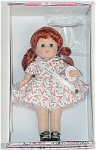 1999 Vogue Century Collection Miss 1950s 8 inch hard vinyl Ginny doll has red hair and moving brown eyes. Her decade's costume consists of a peach and green on white balloon print cotton dress with matching cloth hat, hose, and ribbon with Miss 1950s, and black center-snap shoes. Included is a heart-shaped stand that says 'Ginny' and a doll-sized comb and brush. Retired doll is new and mint-in-the-box, though one of dolls was displayed behind glass.