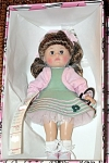 Vogue 2000 Juke Box Ginny doll from the Rock and Roll Collection, 8 inch hard vinyl modern Ginny doll, long brown hair, and brown moving eyes. She is wearing an apple green jumper with an applique musical staff, and music notes, pink inside lining and attached petticoat, pink trim, pink sweater around shoulders with gold sweater chain, multicolor pastel hair ribbon, pink and white bee-bop shoes, middle right. Dress has attached white net slip with gold piping hem. A plastic heart shaped doll stand and doll-sized comb and brush are included.  Retired doll style is new and mint-in-the-box.