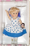 Vogue 2000 1950s-inspired Rock and Roll Collection, Blueberry Thrill Ginny Doll. This 8 inch hard vinyl modern Ginny doll has blonde rooted hair styled in a ponytail with blue scarf and blue moving eyes. Her ensemble includes a blueberry blue polka-dot jumper with rick-rack trim, white net attached petticoat with blue hemline, and white center-snap shoes. A doll-sized comb and brush and heart-shaped plastic 'Ginny' stand are included. This retired doll is new and mint-in-the-box.
