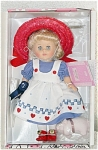 Vogue August Modern Ginny Doll from the 2000 Calendar Collection is ready for State Fair. She has blonde rooted hair and moving blue eyes. Her ensemble includes a red straw hat, a blue dress with white pinafore with red hearts and blue trim, and red center-snap shoes. She comes with a blue ribbon that she won at the fair and an adorable little cloth pig. New mint-in-the-box old stock includes a plastic 'Ginny' stand and doll-sized comb and brush.