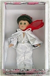 Vogue Ginny 2001 Teen Idol Ginny from the 1950s-inspired Rock n Roll series, is an 8 inch hard vinyl modern Ginny doll with brunette hair with red hair ribbon, and moving green eyes. Her outfit looks like Elvis Presley's performance costumes. It includes a white satin jumpsuit with silver waist and rhinestones, a shiny white cape, a red scarf, and shoes to match. Retired doll is new and mint-in-the-box with doll-sized comb and brush.